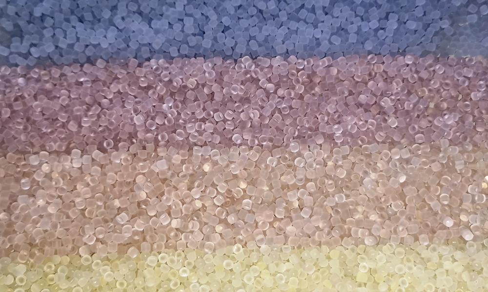 Nahaufnahme von gelbem, orangen, lila- und rosafarbendem PVC Granulat